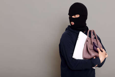 A young thief male dressed in a black hoodie with a disguised face runs away after stealing with other people's belongings, bag, laptop, wallet. Look around, be afraid of being caught, copy-space.