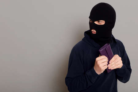 Frightened guy thief dressed in a black hoodie, stole a wallet and runs away looking back, afraid to be caught, copy space, isolated on gray background. 版權商用圖片