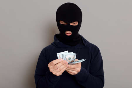 Swindler thief man counts stolen money, wears a black sweater, poses with a disguised face, a criminal breaks the law and takes money from other people, isolated over gray background. 版權商用圖片