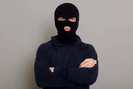 Self-confident criminal male posing isolated on a gray background, wearing a black hoodie and a bandit mask, looking at the camera, holding his hands folded on his chest.