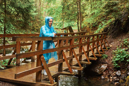 Young beautiful girl, dressed in blue raincoat, stands on wooden bridge, looking far away, enjoying nature, admires the beauty of the forest, rainy day. Outdoor full length portrait.