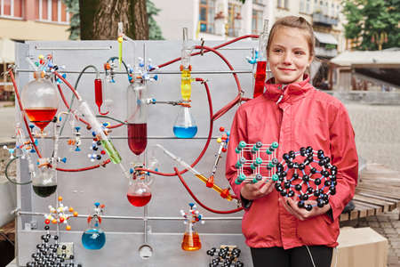 Cute school-age girl poses near a model with a chemical process, test tubes with colored liquids, holds a model of atoms and molecules in her hands, dressed in a red jacket. Outdoor portrait.