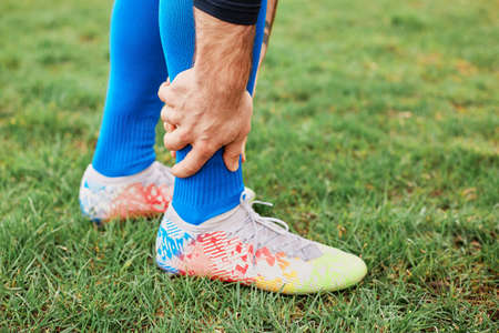 Injured unknown footballer in blue socks and football boots holds his hand on the ankle, feels pain, damaged ligaments during a training session or a match.