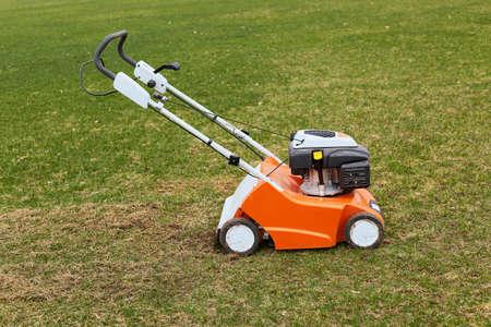 Orange grasscutter standing on ground on green grass, special equipment for trimming grass, grass-mower