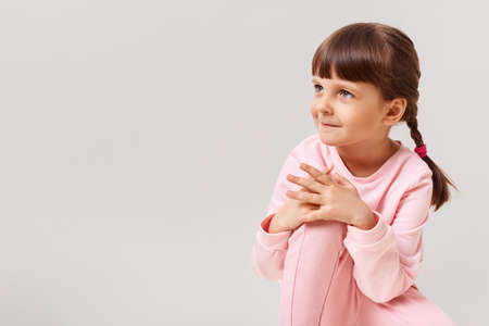 Beautiful cute little girl looks to the side with interest, dressed in pink clothes, has dark hair and two pigtails, copy space for advertisement, isolated over white background. 版權商用圖片