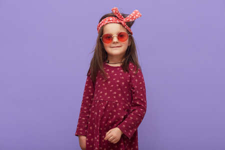 Charming little hipster fashionable girl dressed in burgundy dress, red headband and stylish glasses looking at camera, posing isolated on a purple background