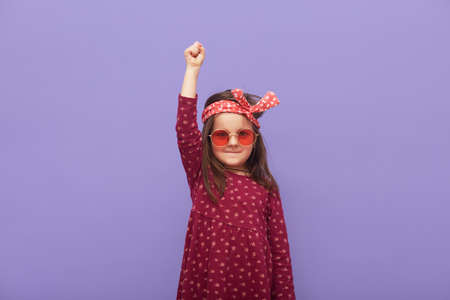 Little fashionable rebel girl dressed in dress, hair band and stylish glasses looks at camera with a grave expression on her face and raised fist up, child defends her rights on purple background