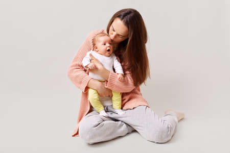Young beautiful attractive mother holding and kissing newborn baby while sitting on floor, dark haired female wearing casual attire, isolated over white background.