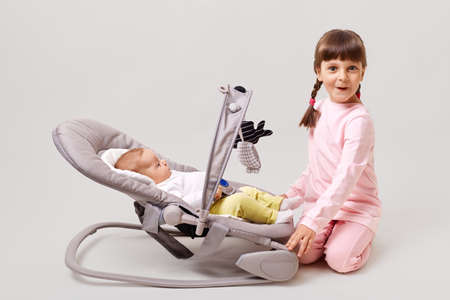 Adorable dark-haired girl with pigtails plays with newborn sister or brother who is lying in bouncer chair, kid looks at camera with surprised and enthusiastic look, isolated over white background.