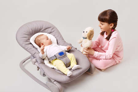 A little dark-haired girl with pigtails is playing with her newborn sister or brother who is lying in a baby rocking chair, showing a small soft toy, isolated over white background.
