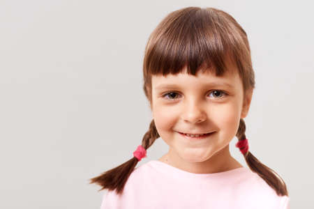 Closeup portrait of little cute girl indoors, child looking at camera with a happy smile, a positive girl with pigtails, dressed in pink clothes, isolated over white background. 版權商用圖片