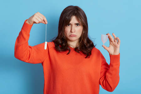 Sad dark haired young adult female in orange sweater posing with menstrual cup and tampon in hands, being upset, being about to cry, isolated over blue background.