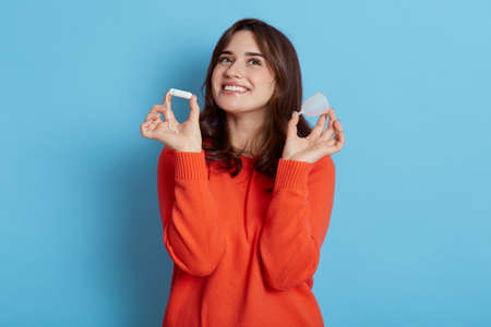 Happy young adult beautiful woman wearing casual attire, looking up with dreamy and satisfied facial expression, holding in hands tampon and menstrual cup, isolated over blue background.