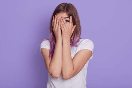 Woman cover her face posing on purple background.