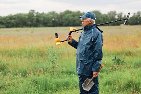 Gray haired senior treasure hunter posing with shovel and metal detector on his shoulder looking away, choosing place for searching coins or other artifacts. Reklamní fotografie