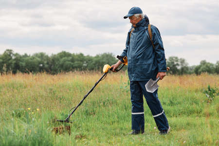 Full length outdoor portrait of numismatist in jacket and cap, holding in hands shovel and metal detector, looking for gold or historical artifacts in meadow.