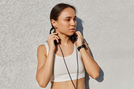 Outdoor portrait of young adult beautiful female wearing white top, listening music during training, keeping hands on headphones, looking away with pensive facial expression. Archivio Fotografico