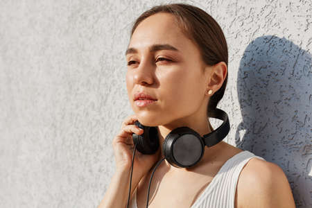 Portrait of dreamy brunette woman wearing white top and having headphones over neck, looking away with pensive facial expression, posing against gray wall outdoor. Archivio Fotografico