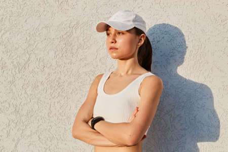 Portrait of serious confident female wearing white top and visor cap, standing isolated over gray wall outdoor with folded hands, looking in distance, sporty woman after work out.