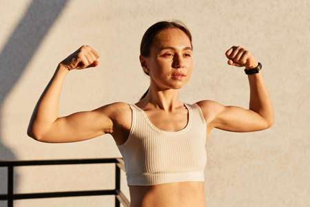 Outdoor shot of young female athlete flexing muscles, showing strong arm biceps, healthy body, productive training outside, wearing stylish white top, looks confident.