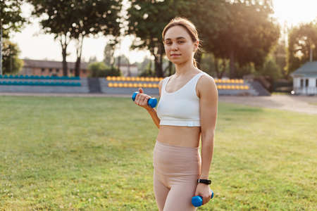 Young adult confident female wearing sporty white top and beige leggins standing in stadium with dumbbells in hands, looking directly at camera, work out outdoor. 版權商用圖片