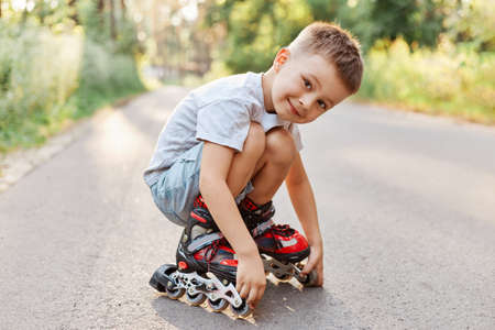 Boy in roller skating sitting on the road, looking at camera with smile, wearing white t-shirt and short, child squats while having rest rollerblading.