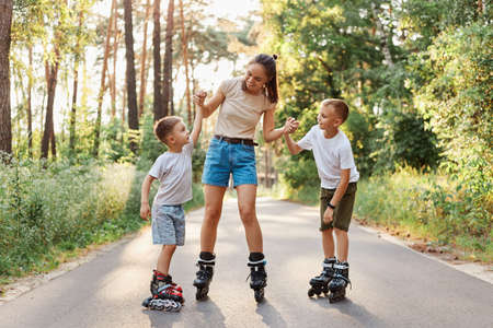 Young mother with her children rollerblading in summer park, holding arms her sons and smiling happily, spending time and having fun together, family wearing casual clothing.