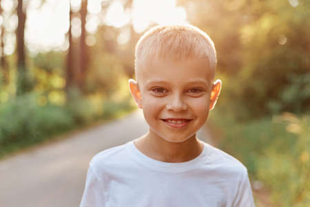 Portrait of a blonde happy child boy outdoors on warm sunny summer day, wearing white casual style T-shirt, looking at camera, expressing positive emotions.