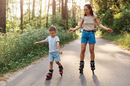 Portrait of smiling mother and son learn to roller skate, mom with child having fun on roller skates in summer park together, concentrated kid rollerblading, mommy rejoices his success.