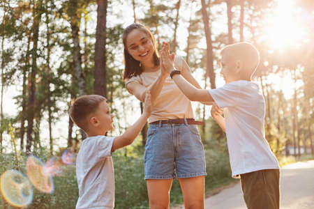 Mother giving her elder son a high five with toothy smile, smaller boy wants to clap mommy's hand, raised arm, family expressing positive emotions spending time together. 版權商用圖片