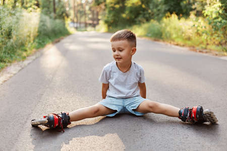 Outdoor shot of happy little boy sitting in twine on asphalt road in roller skating, looking smiling aside, learning to roller skating in summer park.
