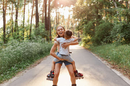 Outdoor shot of mother with little boy kid roller skating in summer park, mother holding child in hands, hugging and smiling with happiness, enjoying spending time with son.