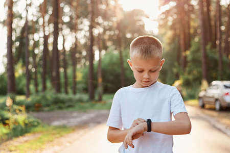 Little blonde boy using fitness bend touching button and touchscreen while posing outdoor in park, touching button and setting smart watch before running on road.