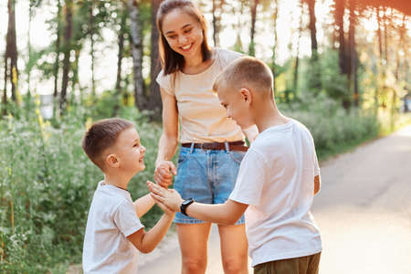 Family having fun while walking in summer park and laughing, little boy gives a high five to his elder brother, happy children standing near their smiling mother. 版權商用圖片