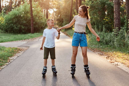 Outdoor full length portrait of happy brunette female holding son's hand and rollerblading together, family wearing casual style clothing, spending time in park. 版權商用圖片