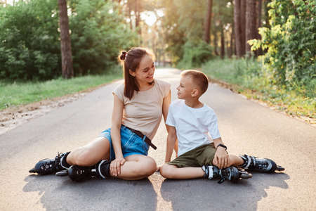 Outdoor shot of beautiful woman sitting on asphalt road with her son, wearing casual clothing and roller skates, family having rest rollerblading, looking at each other and talking.