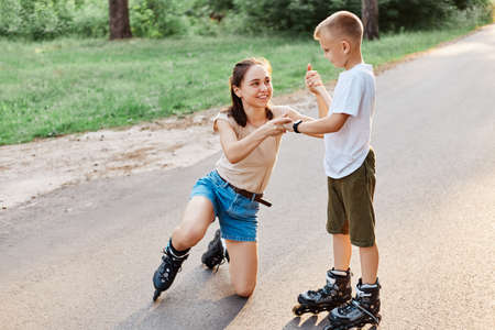 Little cute boy help mother to stand up from road after falling down in roller skates, smiling woman looking at her child, family weekend in summer park. 版權商用圖片