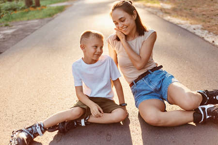 Mother and son in roller skates sitting on a road, mommy talking with her little boy, enjoying beautiful nature and fresh air, active weekends together. 版權商用圖片