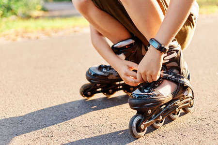 Close up portrait of unknown child squats on road and fixing laces on roller blades before skating, faceless kid having fun outdoor, rollerblading, playing alone.
