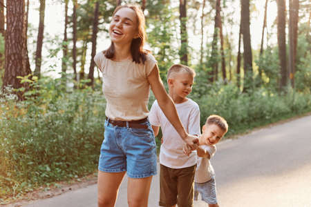 Mother with two little sons playing outdoor in nature, dark haired woman in t-shirt and short spending time with her children in sunny summer day, family, childhood.
