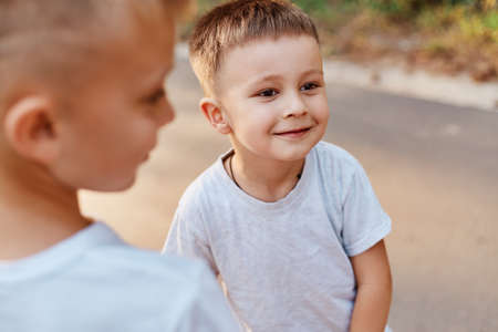 Portrait of two boys, siblings, brothers and best friends wearing white casual style t-shirts posing outdoors, spending free time together, children expressing happiness. 版權商用圖片