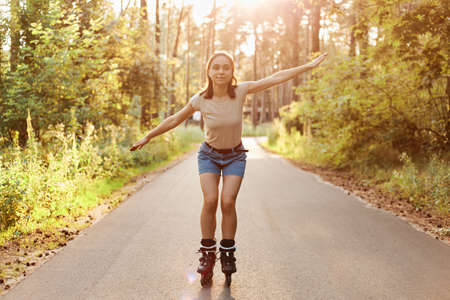 Full length portrait of beautiful brunette woman wearing t shirt and jeans short rollerblading in park, spreading her hands aside like flying, looking directly at camera.