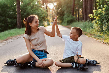 Outdoor shot of happy family mother and son wearing casual style clothing and roller skates sitting on asphalt road in park, boy giving to mom high five, looking at each other with smile.