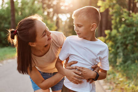 Outdoor shot of attractive woman mother hugging her little son wearing in white t shirt, mommy looking at boy with smile, spending time together in summer park. 版權商用圖片