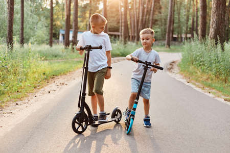 Outdoor shot of two brother wearing casual clothing riding scooters in summer park, spending time happily, having fun together in active way, happy childhood. 版權商用圖片