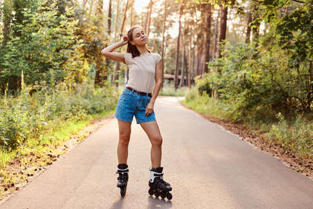 Healthy young adult dark haired woman wearing beige t shirt and jeans shirt riding on roller skates on asphalt road in park, enjoying active ti, e, keeps eyes closed.