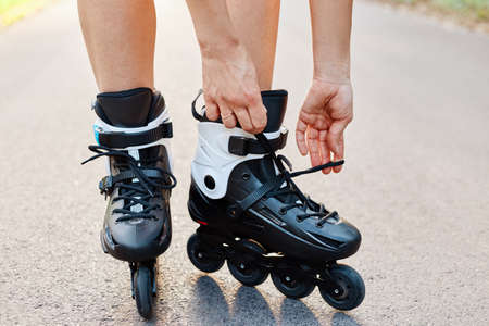 Close-up of an anonymous woman hands fixing laces on roller blades during skating, unknown female on road in summer park, rollerblading, active lifestyle.