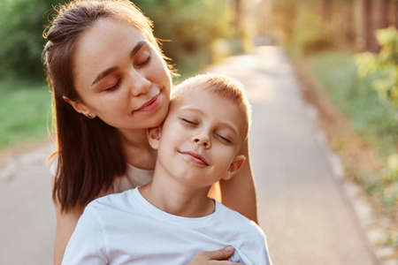 Outdoor portrait of happy family, mother hugging her son, enjoying to spend time together, keeping eyes closed, walking in summer park, motherhood, childhood.