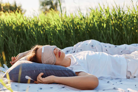 Portrait of woman wearing sleeping mask and white t shirt lying on soft bed in the middle of green field or meadow, female sleeps outdoors in summertime.
