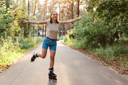 Full length portrait of attractive slim woman wearing casual style attire riding roller skates, pretending she is flying, raised arms, looking away with toothy smile. 版權商用圖片